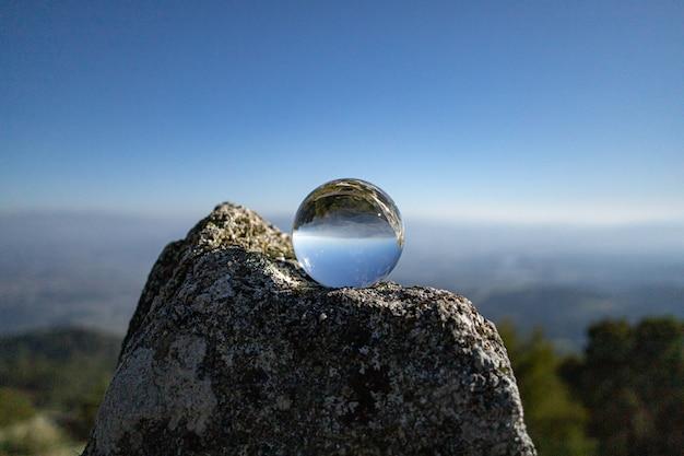 Nahaufnahme einer kristallkugel auf dem felsen mit reflexionen des himmels und der felsen