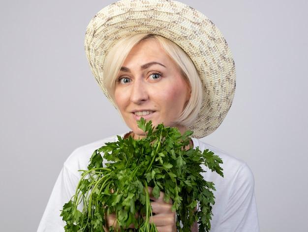 Nahaufnahme einer lächelnden blonden gärtnerin mittleren alters in uniform mit hut, die zwei büschel koriander hält