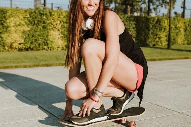 Nahaufnahme einer lächelnden frau, die in park skateboard fährt
