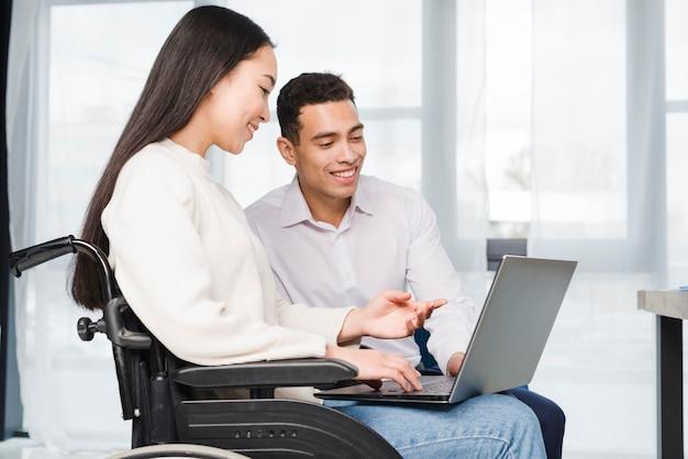 Nahaufnahme einer lächelnden jungen frau, die auf dem rollstuhl zeigt zu ihrem kollegen auf laptop sitzt