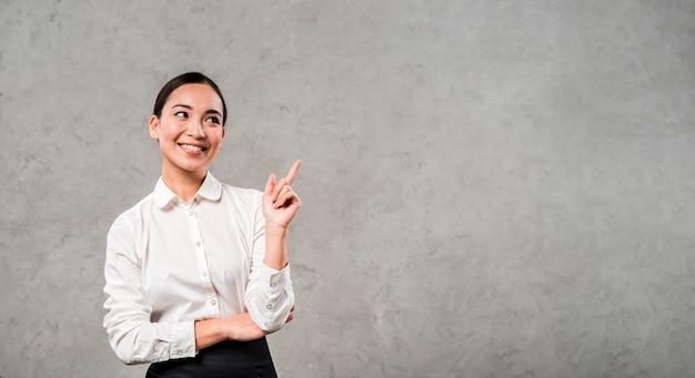 Nahaufnahme einer lächelnden jungen geschäftsfrau, die ihren finger aufwärts stehend gegen betonmauer zeigt