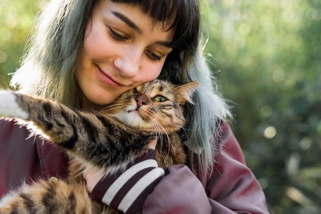 Nahaufnahme einer lächelnden schönen frau, die ihre katze der getigerten katze im garten umfasst