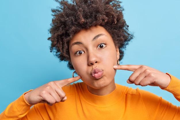 Nahaufnahme einer lockigen jungen frau, die wangen drückt und den atem anhält, macht eine lustige grimasse mit lockigem haar, das in einem lässigen orangefarbenen pullover isoliert über blauer wand gekleidet ist. gesichtsausdrücke konzept