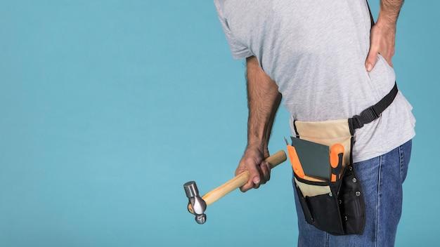 Nahaufnahme einer männlichen arbeitskraft, die unter rückenschmerz hält, der hammer hält