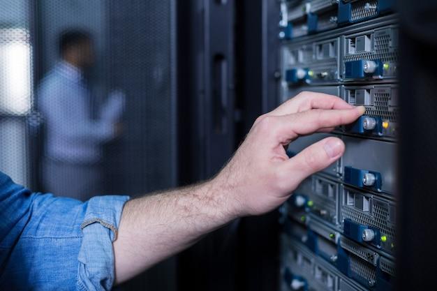 Nahaufnahme einer männlichen hand, die den knopf drückt, während sie mit dem speicherdatensystem im serverraum arbeitet