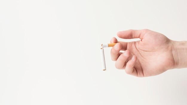 Nahaufnahme einer männlichen hand, die gebrochene zigarette anhält