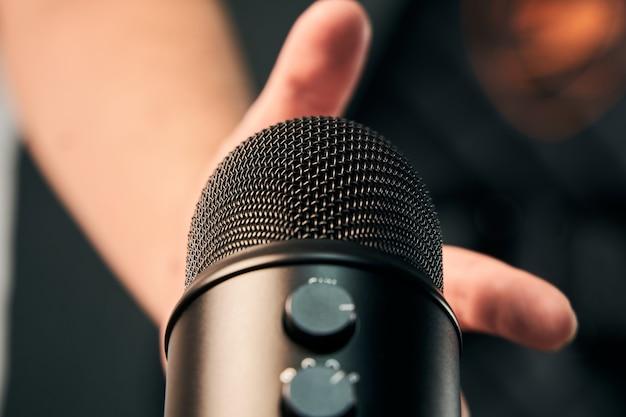 Nahaufnahme einer männlichen hand, die gerade dabei ist, ein schwarzes mikrofon zu nehmen