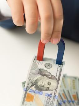 Nahaufnahme einer männlichen hand, die magnet hält und geld vom stapel zieht
