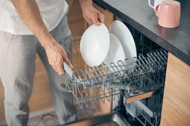 Nahaufnahme einer männlichen person, die in der nähe der spülmaschine steht und teller in der küche abstützt Premium Fotos