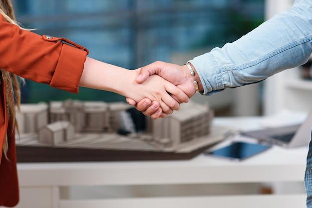 Nahaufnahme einer männlichen und einer weiblichen hand, die sich nach der unterzeichnung einer guten geschäftsvereinbarung gegenseitig schütteln. erfolgreiches geschäftskonzept.