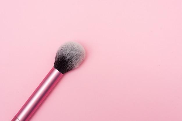 Nahaufnahme einer make-up-bürste. make-up-pinsel für pudergrundierung lokalisiert auf rosa hintergrund