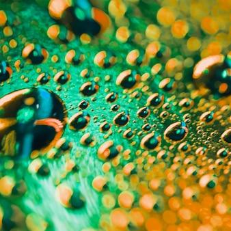 Nahaufnahme einer makrophotographie der grünen und orange wassertröpfchen