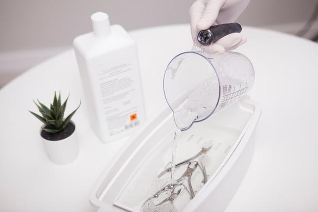 Nahaufnahme einer maniküre, die mit einer nagelzange einen flüssigen sterilisator in einen behälter gießt