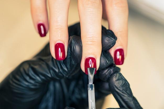 Nahaufnahme einer maniküre in schwarzen handschuhen, die ein muster mit einem pinsel auf die nägel aufträgt