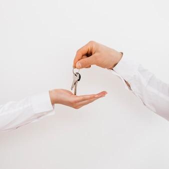 Nahaufnahme einer mannhand, die der frau schlüssel gibt