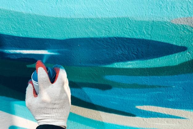Nahaufnahme einer mannhand in einem handschuh hält einen ballon mit farbe