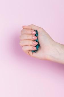 Nahaufnahme einer menschlichen hand, die grüne kapsel hält