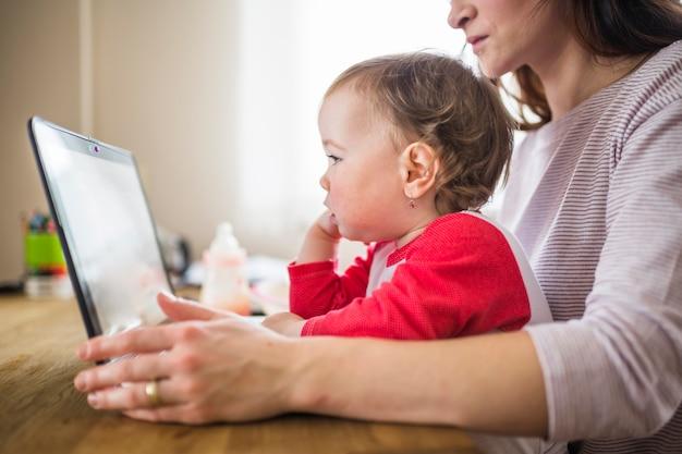 Nahaufnahme einer mutter mit dem netten baby, das laptop betrachtet