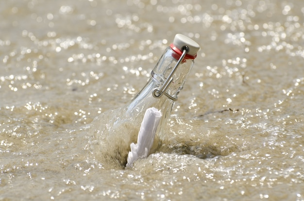 Nahaufnahme einer nachricht in einer flasche in einem sand mit wasser an einem sonnigen tag