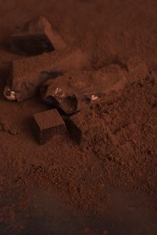 Nahaufnahme einer natürlichen hausgemachten dunklen schokolade, die mit pulver bedeckt ist