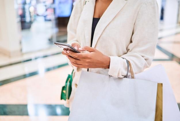 Nahaufnahme einer nicht erkennbaren frau mit handy und taschen beim einkaufen