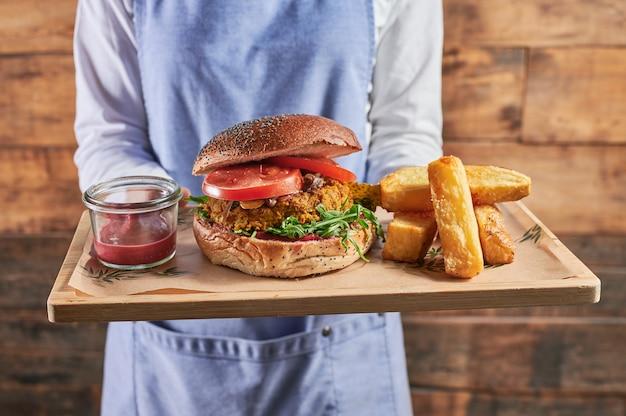 Nahaufnahme einer nicht erkennbaren kellnerin, die einen großen veganen linsenburger mit rote-bete-ketchup serviert