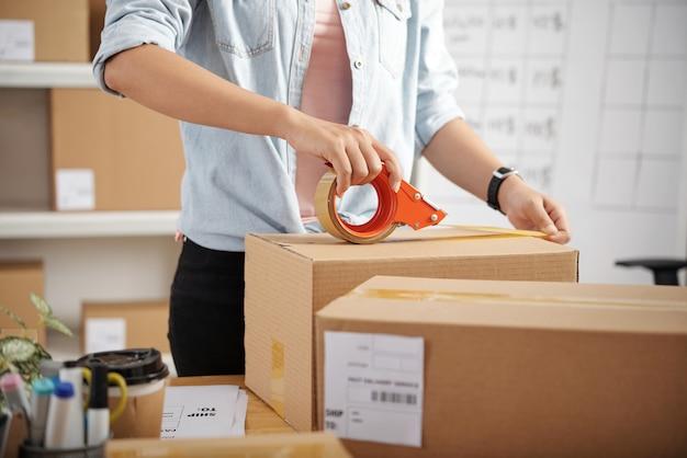 Nahaufnahme einer nicht wiederzuerkennenden frau, die mit paketen am tisch steht und vor der lieferung den paketkasten aufkleistert