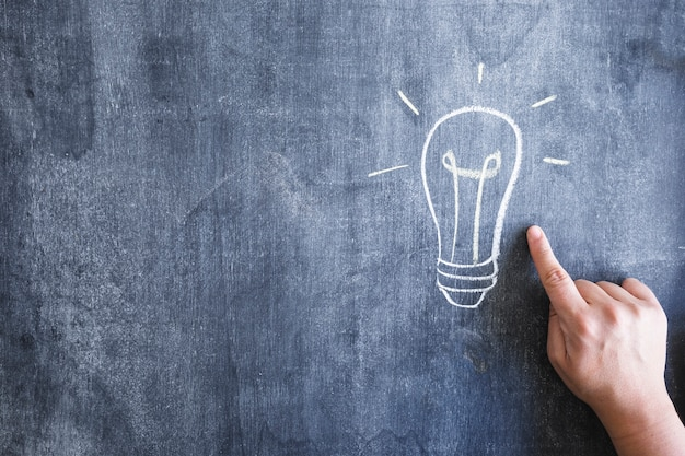 Nahaufnahme einer person, die an hand gezeichnete glühlampe des fingers über der tafel zeigt
