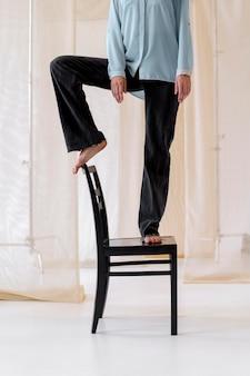 Nahaufnahme einer person, die auf einem stuhl steht