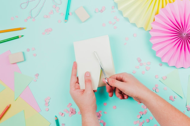 Nahaufnahme einer person, die das papier mit der schere auf aquamarinem hintergrund schneidet