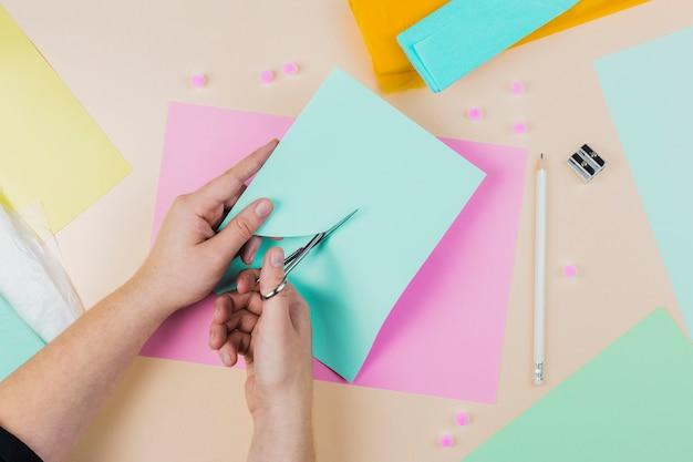 Nahaufnahme einer person, die das papier mit scissor auf farbigem hintergrund schneidet