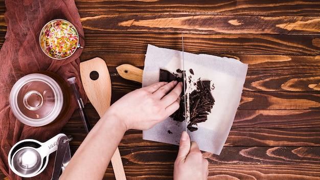 Nahaufnahme einer person, die den schokoriegel mit messer auf papier über dem holztisch schneidet