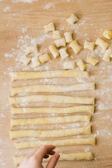 Nahaufnahme einer person, die den teig für das vorbereiten der teigwaren gnocchi anordnet