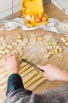 Nahaufnahme einer person, die den teig mit messer für die zubereitung der selbst gemachten teigwaren gnocchi auf hölzernem schreibtisch schneidet