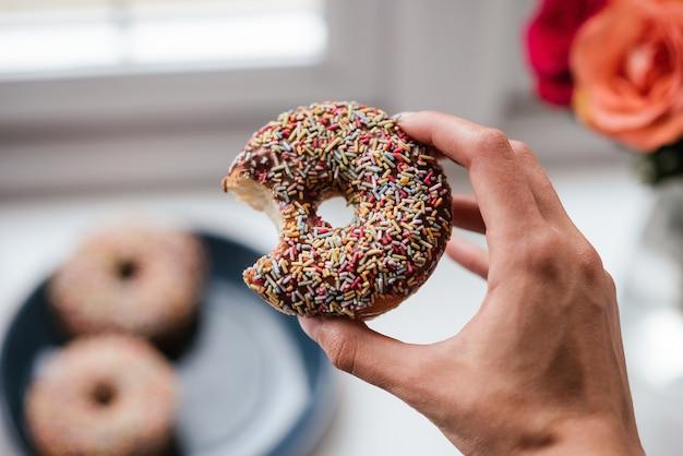 Nahaufnahme einer person, die einen donut hält