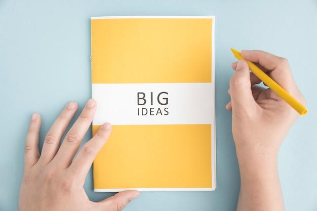 Nahaufnahme einer person, die gelben zeichenstift mit großem ideenbuch auf blauem hintergrund hält