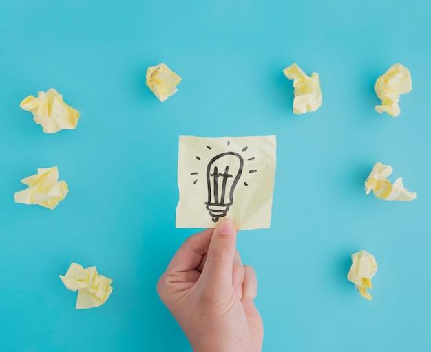 Nahaufnahme einer person, die glühlampepapier der idee mit zerknittertem ball von papieren auf blauem hintergrund hält