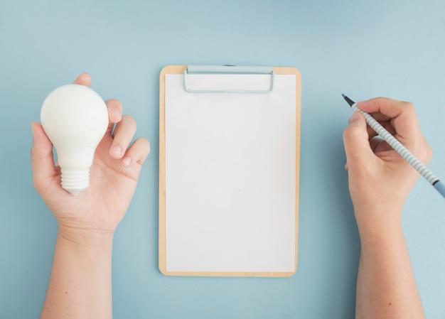 Nahaufnahme einer person, die glühlampeschreiben mit filzstift auf klemmbrett hält
