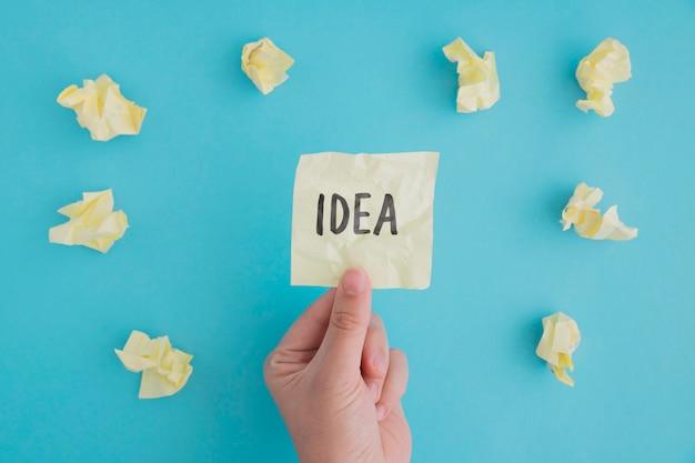 Nahaufnahme einer person, die ideenpapier mit zerknittertem ball von papieren auf blauem hintergrund hält