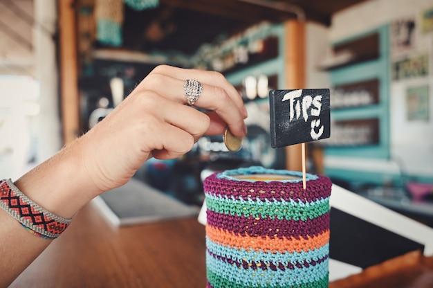 Nahaufnahme einer person, die in einem café unter den lichtern trinkgeld gibt