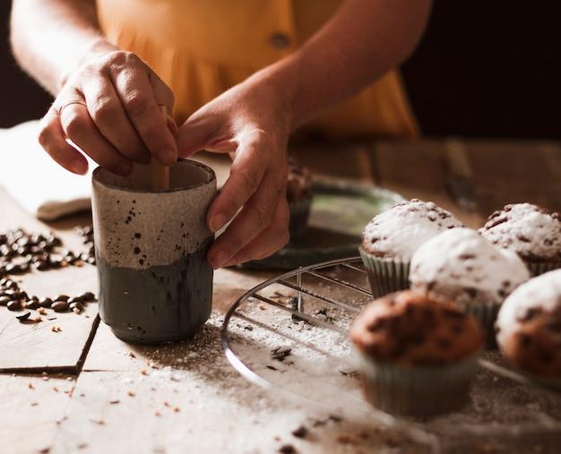Nahaufnahme einer person, die kleinen kuchen vorbereitet