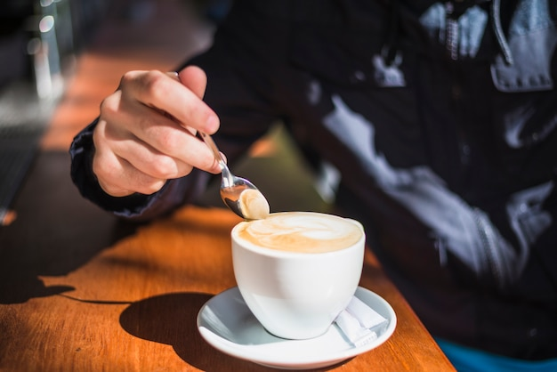 Nahaufnahme einer person, die löffel über dem cappuccino oder dem latte mit schaumigem schaum hält