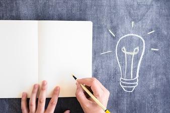 Nahaufnahme einer Person, die mit gelbem Filzstift auf Notizbuch gegen die Tafel schreibt