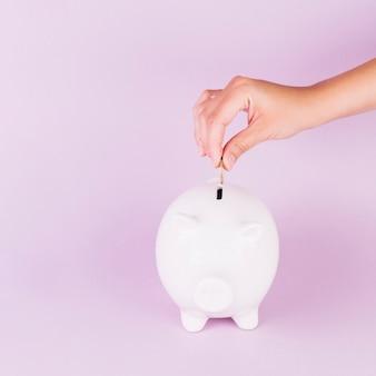 Nahaufnahme einer person, die münze in weißes piggybank gegen rosa hintergrund einfügt