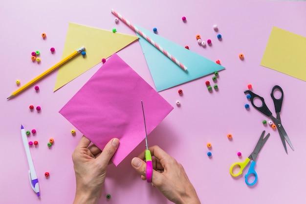 Nahaufnahme einer person, die papier mit scissor über dem rosa hintergrund schneidet