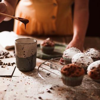 Nahaufnahme einer person, die schmelzschokolade im glas mit kleinen kuchen vorbereitet