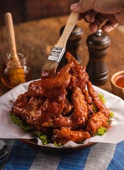 Nahaufnahme einer person, die soße auf köstlich gekochte hühnerflügel in einer schüssel auf dem tisch setzt