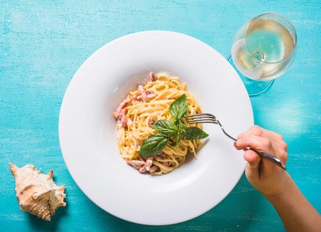 Nahaufnahme einer person, die spaghettis mit fleisch und basilikum isst, treiben auf platte blätter