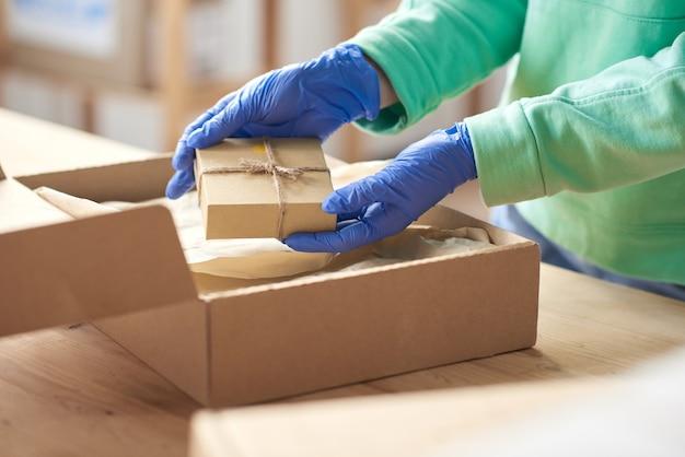 Nahaufnahme einer person in schutzhandschuhen, die vor der zustellung wenig geschenk für den kunden in das paket legt