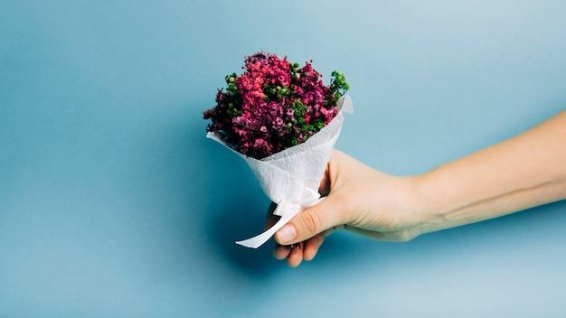 Nahaufnahme einer personenhand, die schönen blumenstrauß gegen blauen hintergrund hält